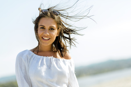 female beauty: Beautiful young woman posing on a windy summer day on the beach