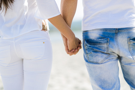 parejas felices: Pareja romántica de la mano en una playa Foto de archivo