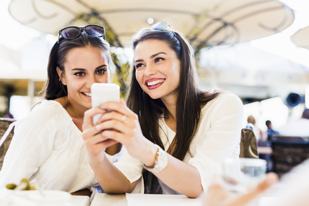 niñas sonriendo: Dos chicas jóvenes hablando y sonriente durante la pausa para el almuerzo