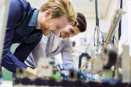 electronics: Two young handsome engineers working on electronics components and fixing broken chips Stock Photo
