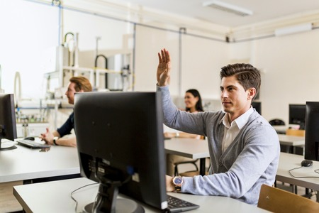 adult education: Young handsome man sitting in front of a pc raising hand Stock Photo