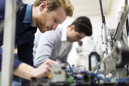 Two young handsome engineers working on electronics components and fixing broken chips Stock Photo