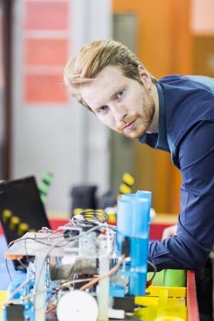 electricista: Hombre ingeniero eléctrico programar un robot durante la clase de robótica