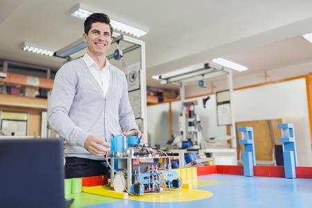 class maintenance: Male electrical engineer programming a robot during robotics class