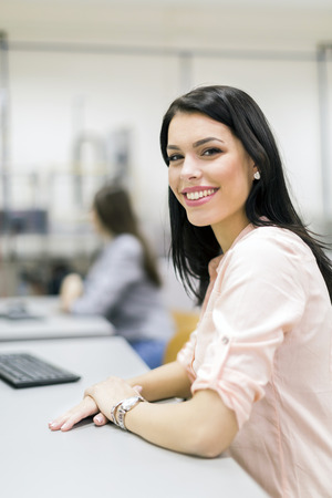 career young: Young beautiful woman smiling happily in a classroom equipped with computers