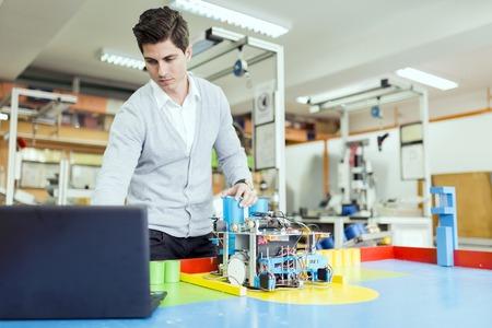 estudiantes: Hombre ingeniero el�ctrico programar un robot durante la clase de rob�tica