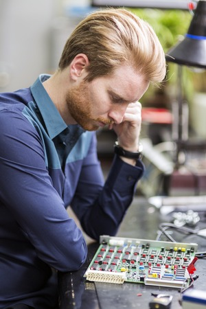 electronic board: Young handsome man thinking while soldering a circuit board and working on fixing hardware