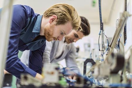 electricista: Dos j�venes ingenieros hermoso que trabaja en componentes electr�nicos y de fijaci�n virutas rotos