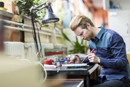 若いハンサムな男回路基板をはんだ付けし、ハードウェアを取りつけることに取り組んで