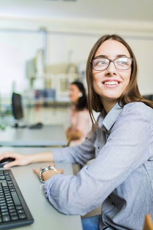 adult education: Young beautiful girl working on a computer in a classroom