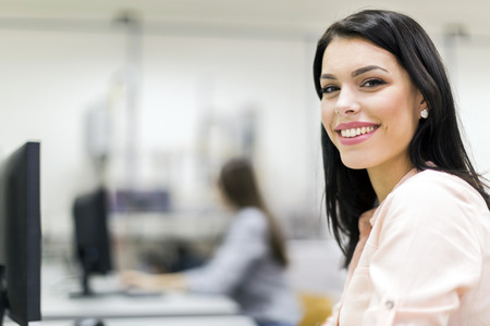 university classroom: Young beautiful woman smiling happily in a classroom equipped with computers