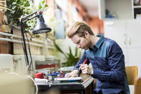 ingenieria industrial: Hombre hermoso joven que soldar una placa de circuito y de trabajo en la fijaci�n de hardware Foto de archivo