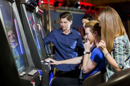 Grupo de jóvenes de los juegos de azar en un casino de juego ranura y varias máquinas
