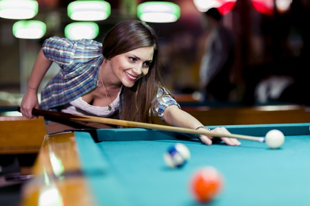 billard: Young beautiful young lady aiming to take the snooker shot while leaning over the table in a club