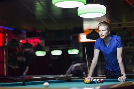 bola de billar: Apuesto jugador de billar joven inclinado sobre la mesa en un bar con una hermosa iluminaci�n ambiental