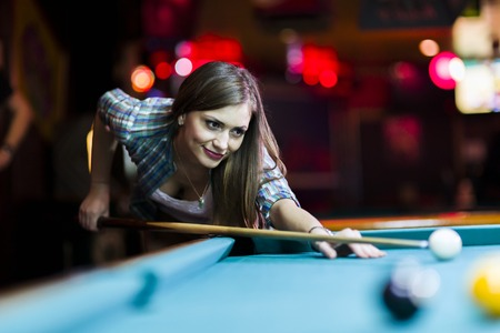 leaning over: Young beautiful young lady aiming to take the snooker shot while leaning over the table in a club