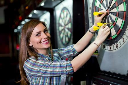 Jonge mooie vrouw spelen darts in een club en glimlachen