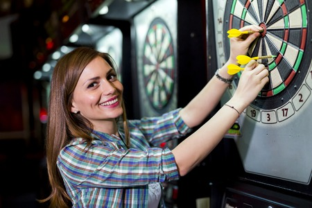 dart on target: Young beautiful woman playing darts in a club and smiling Stock Photo