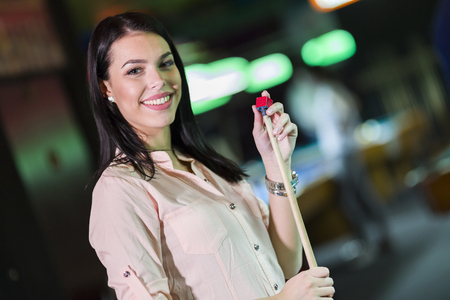 snooker cue: Young beautiful woman chalking the snooker cue and smiling in a club Stock Photo