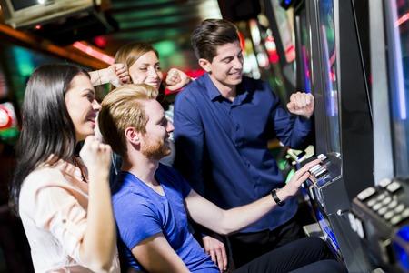 slot machines: Grupo de jóvenes de los juegos de azar en un casino de juego ranura y varias máquinas