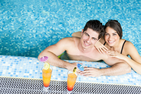 bikini couple: Couple drinking a cocktail by the swimming pool and relaxing