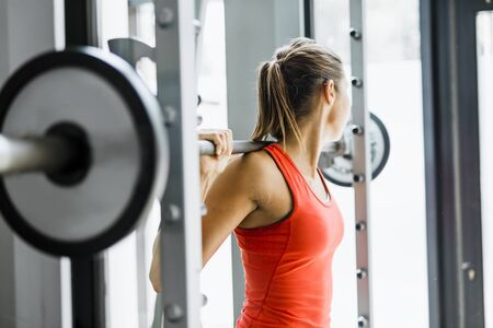 Focused young beautiful woman lifting weights in a gym Stock Photo