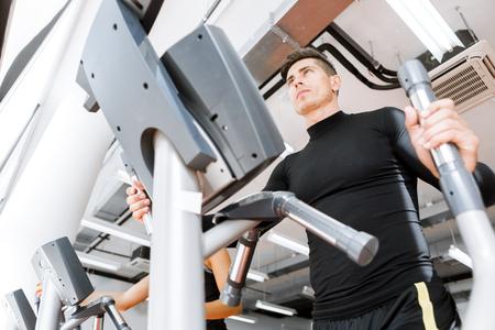 eliptica: Joven varón del ajuste que se resuelve en una elíptica entrenador en un gimnasio Foto de archivo