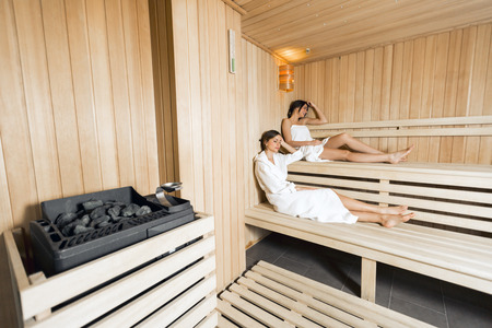 finland sauna: Sauna heater in a cozy sauna and girls relaxing in the background
