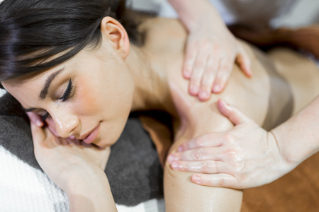 massaged: Beautiful woman lying on a massage table and relaxing while being massaged