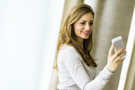 woman on couch: Beautiful brunette using a phone in a stylish house and smiling Stock Photo