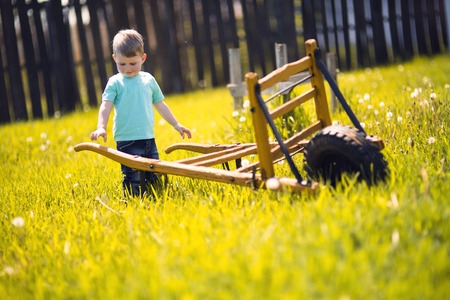 fall harvest: Little boy working in the fields  and pushing a wheelbarrow