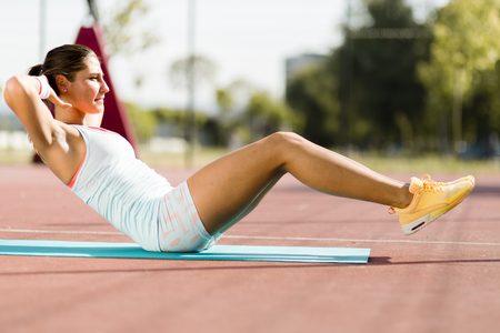 situps: Young beautiful woman exercising outdoors by doing situps