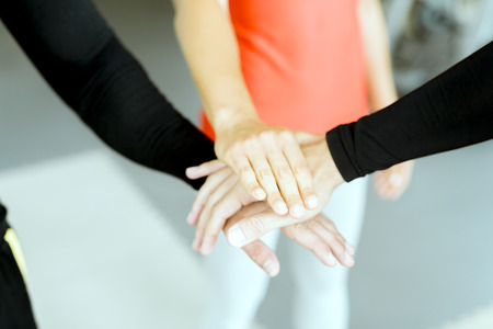 three hands: Three hands placed on top of each other between sportsmen as a sign of teamwork and unity