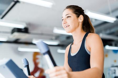 eliptica: Señora joven hermosa usando el entrenador elíptico en un gimnasio en un estado de ánimo positivo Foto de archivo