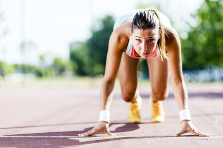 caras: Atleta femenina hermosa que consigue listo para la carrera durante el verano