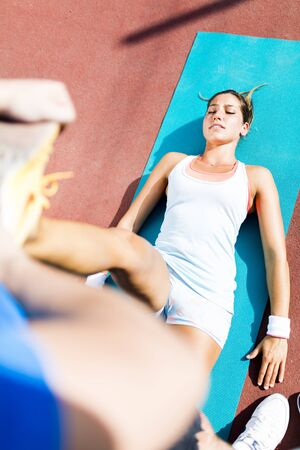 muscle spasm: Young beautiful sportswoman having a strain and being stretched by trainer Stock Photo