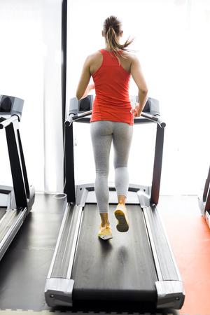 treadmill: Beautiful young woman running on a treadmill infitness center Stock Photo