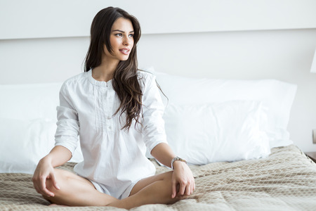 yoga pillows: Beautiful brunette in a white shirt tailor seat posing on a bed and relaxing