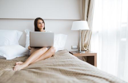 mujeres morenas: Joven y bella mujer con las piernas largas atractivas en camisa usando un cuaderno en la cama