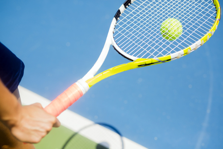 Raquet: Closeup of a player holding the racquet and preparing for the serv at the baseline Stock Photo