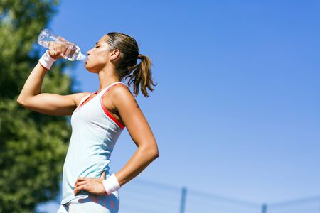 tomando agua: Young beautiful athlete drinking water after exercising to revitalize Foto de archivo