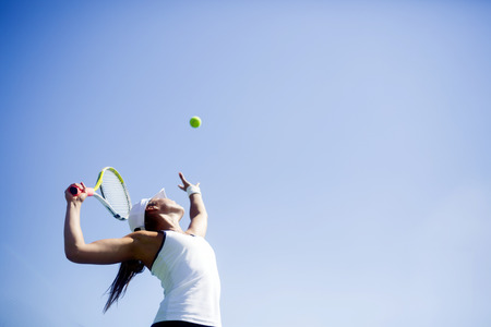 lifestyle woman: Beautiful female tennis player serving outdoor