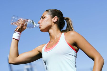 revitalize: Young beautiful athlete drinking water after exercising to revitalize Stock Photo