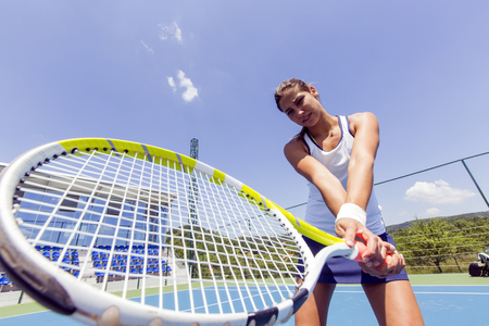 forehand: Beautiful female tennis player in action, hitting a forehand