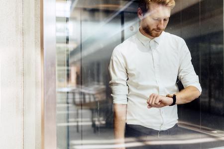 Geschäftsmann Überprüfung Watch während er in der glasüberdachten Aufzug