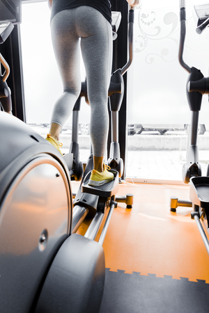 elliptical: Closeup shot of legs of a female using elliptical trainer in a gym