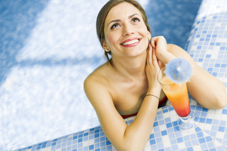 hot weather: Beautiful woman in a pool with a cocktail next to her Stock Photo
