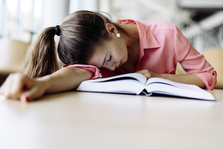 sleeping at desk: Beautiful pretty woman fallen asleep on the table while studying and reading a book Stock Photo