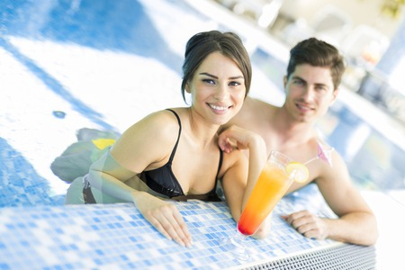 fresh girl: Couple drinking a cocktail by the swimming pool and relaxing