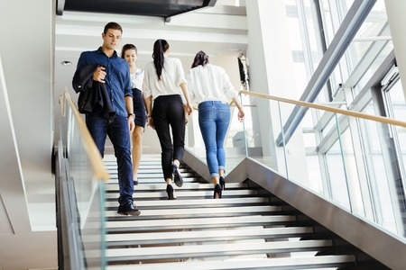 Group of businessman walking and taking stairs in an office building Stock Photo